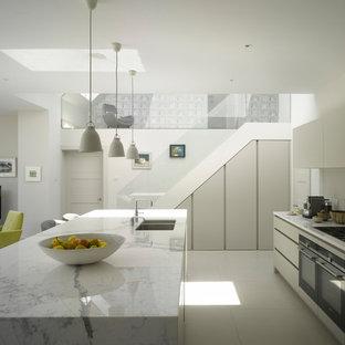 ロンドンの広いコンテンポラリースタイルのおしゃれなキッチン (ダブルシンク、フラットパネル扉のキャビネット、グレーのキャビネット、大理石カウンター、パネルと同色の調理設備、セラミックタイルの床、白い床、白いキッチンカウンター) の写真