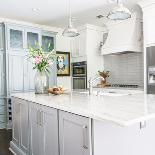Mid-sized farmhouse kitchen appliance - Kitchen - mid-sized country u-shaped brown floor and medium tone wood floor kitchen idea in Atlanta with a farmhouse sink, shaker cabinets, white cabinets, ceramic backsplash, stainless steel appliances, an island, gray backsplash, quartzite countertops and gray countertops