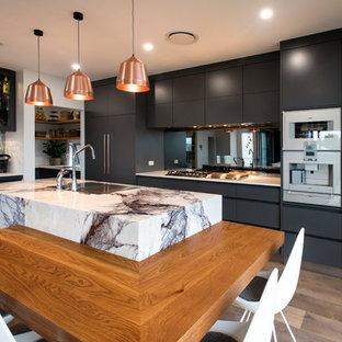 ブリスベンのコンテンポラリースタイルのおしゃれなキッチン (グレーのキャビネット、大理石カウンター、ミラータイルのキッチンパネル、無垢フローリング、アンダーカウンターシンク、フラットパネル扉のキャビネット、白い調理設備、茶色い床、白いキッチンカウンター) の写真