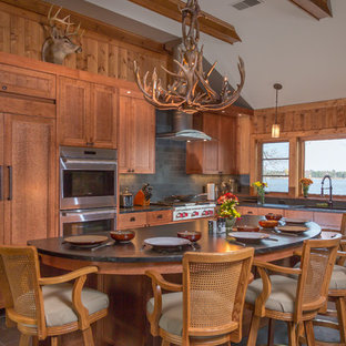 This is an example of a country l-shaped open plan kitchen in Minneapolis with an undermount sink, shaker cabinets, medium wood cabinets, quartz benchtops, grey splashback, stainless steel appliances, slate floors, with island and slate splashback.