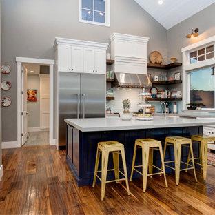 Modelo de cocina en L, moderna, grande, abierta, con armarios estilo shaker, puertas de armario blancas, suelo de madera en tonos medios y una isla