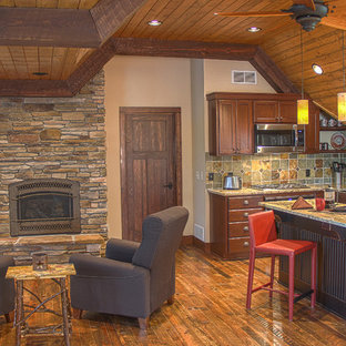 This is an example of a country kitchen in Minneapolis with a farmhouse sink, raised-panel cabinets, brown cabinets, granite benchtops, multi-coloured splashback, slate splashback, stainless steel appliances, medium hardwood floors, with island and brown floor.