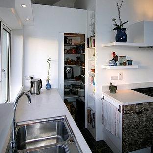 他の地域の中サイズのコンテンポラリースタイルのおしゃれなキッチン (ドロップインシンク、フラットパネル扉のキャビネット、ヴィンテージ仕上げキャビネット、コンクリートカウンター、白いキッチンパネル、セメントタイルのキッチンパネル、カラー調理設備、スレートの床、白いキッチンカウンター) の写真