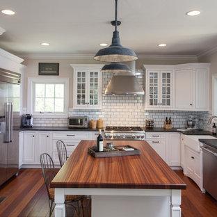 Пример оригинального дизайна: отдельная, п-образная кухня среднего размера в классическом стиле с раковиной в стиле кантри, стеклянными фасадами, белыми фасадами, столешницей из бетона, белым фартуком, фартуком из плитки кабанчик, техникой из нержавеющей стали, полом из бамбука и островом
