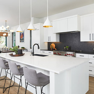 Large contemporary eat-in kitchen appliance - Inspiration for a large contemporary galley medium tone wood floor and brown floor eat-in kitchen remodel in Grand Rapids with an undermount sink, flat-panel cabinets, white cabinets, quartz countertops, black backsplash, ceramic backsplash, an island, white countertops and paneled appliances