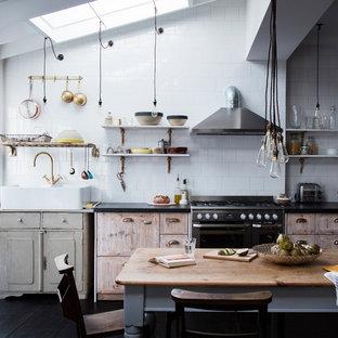 Modelo de cocina comedor lineal, industrial, de tamaño medio, sin isla, con encimera de granito, salpicadero blanco, electrodomésticos de acero inoxidable, encimeras negras, fregadero sobremueble, puertas de armario con efecto envejecido y suelo de madera oscura