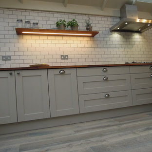 This is an example of a classic kitchen/diner in London with a belfast sink, shaker cabinets, grey cabinets, wood worktops, metro tiled splashback, stainless steel appliances, light hardwood flooring and an island.