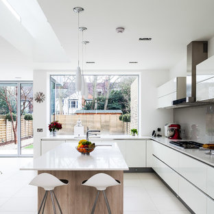 Inspiration pour une cuisine design avec un évier encastré, un placard à porte plane, des portes de placard blanches, une crédence grise, une crédence en feuille de verre, un électroménager en acier inoxydable et un îlot central.