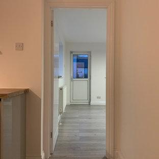 バッキンガムシャーの小さいモダンスタイルのおしゃれなキッチン (シングルシンク、フラットパネル扉のキャビネット、ターコイズのキャビネット、木材カウンター、緑のキッチンパネル、メタルタイルのキッチンパネル、白い調理設備、ラミネートの床、アイランドなし、マルチカラーの床、マルチカラーのキッチンカウンター) の写真