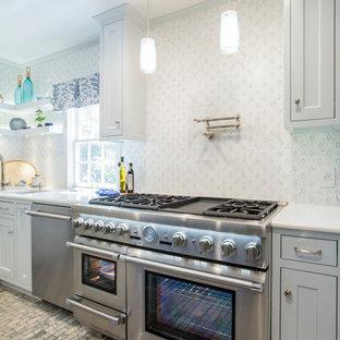 Immagine di una cucina classica di medie dimensioni con lavello a doppia vasca, ante con riquadro incassato, ante grigie, top in vetro riciclato, paraspruzzi multicolore, paraspruzzi con piastrelle a mosaico, elettrodomestici in acciaio inossidabile, pavimento in marmo, isola, pavimento multicolore e top bianco