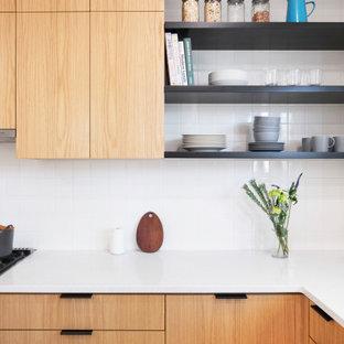 ニューヨークのコンテンポラリースタイルのおしゃれなキッチン (アンダーカウンターシンク、フラットパネル扉のキャビネット、淡色木目調キャビネット、クオーツストーンカウンター、白いキッチンパネル、サブウェイタイルのキッチンパネル、シルバーの調理設備、セメントタイルの床、ピンクの床、白いキッチンカウンター) の写真