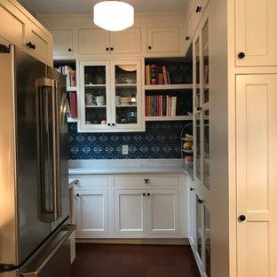Idéer för att renovera ett amerikanskt vit vitt skafferi, med en undermonterad diskho, skåp i shakerstil, vita skåp, bänkskiva i onyx, grönt stänkskydd, stänkskydd i glaskakel, rostfria vitvaror, mellanmörkt trägolv och en köksö
