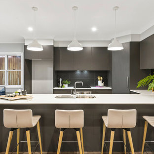 This is an example of a mid-sized contemporary u-shaped open plan kitchen in Other with a single-bowl sink, flat-panel cabinets, grey cabinets, laminate benchtops, grey splashback, ceramic splashback, stainless steel appliances, medium hardwood floors, with island, brown floor and white benchtop.