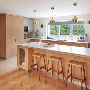 Foto di una cucina classica di medie dimensioni con ante lisce, ante marroni, paraspruzzi grigio, elettrodomestici neri, pavimento in legno massello medio, isola e pavimento marrone