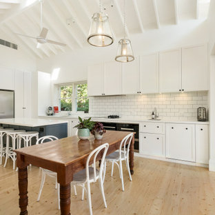Transitional l-shaped eat-in kitchen in Sydney with an undermount sink, shaker cabinets, white cabinets, white splashback, subway tile splashback, black appliances, light hardwood floors, with island, beige floor, white benchtop, exposed beam and vaulted.