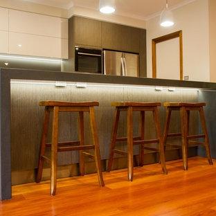 Große Moderne Wohnküche in L-Form mit flächenbündigen Schrankfronten, Quarzwerkstein-Arbeitsplatte, Küchenrückwand in Metallic, Glasrückwand, braunem Holzboden und Kücheninsel in Melbourne