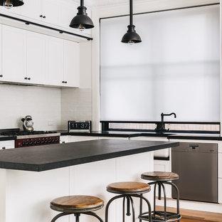 シドニーの大きいインダストリアルスタイルのおしゃれなキッチン (エプロンフロントシンク、シェーカースタイル扉のキャビネット、白いキャビネット、白いキッチンパネル、シルバーの調理設備の、無垢フローリング、茶色い床、黒いキッチンカウンター) の写真