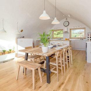 Eklektische Küche mit flächenbündigen Schrankfronten, beigen Schränken, Quarzit-Arbeitsplatte, Küchenrückwand in Weiß, Rückwand aus Keramikfliesen, hellem Holzboden, weißer Arbeitsplatte und gewölbter Decke in Portland Maine