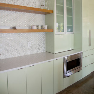 This is an example of a medium sized contemporary open plan kitchen in Miami with flat-panel cabinets, green cabinets, multi-coloured splashback, mosaic tiled splashback, stainless steel appliances, an island and quartz worktops.