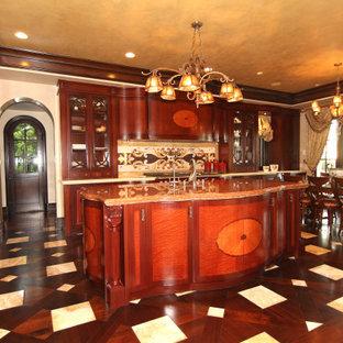 Foto di una cucina mediterranea di medie dimensioni con lavello sottopiano, ante lisce, ante in legno bruno, top in marmo, paraspruzzi beige, paraspruzzi con piastrelle in pietra, elettrodomestici da incasso, parquet scuro, isola, pavimento marrone e top arancione