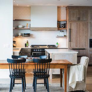 Foto på ett maritimt kök, med öppna hyllor, skåp i ljust trä, vitt stänkskydd, stänkskydd i tunnelbanekakel, svarta vitvaror, ljust trägolv och en köksö