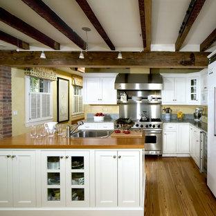 Cette photo montre une cuisine chic avec un placard avec porte à panneau encastré, un électroménager blanc, un plan de travail en bois, un évier posé et des portes de placard blanches.