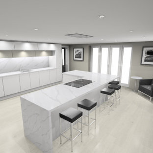 Photo of a large modern eat-in kitchen in Cardiff with an integrated sink, flat-panel cabinets, white cabinets, quartz benchtops, black appliances, porcelain floors, with island, yellow floor and white benchtop.