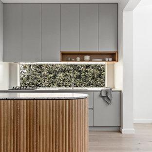 Idéer för ett litet modernt grå kök, med en dubbel diskho, grå skåp, bänkskiva i terrazo, svarta vitvaror, ljust trägolv och en köksö
