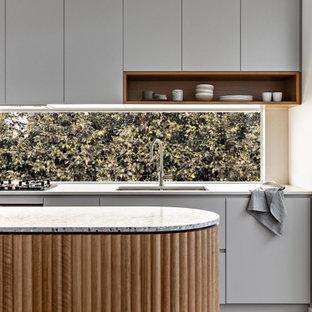 Zweizeilige, Kleine Moderne Wohnküche mit Doppelwaschbecken, grauen Schränken, Arbeitsplatte aus Terrazzo, schwarzen Elektrogeräten, hellem Holzboden, Kücheninsel und grauer Arbeitsplatte in Sydney