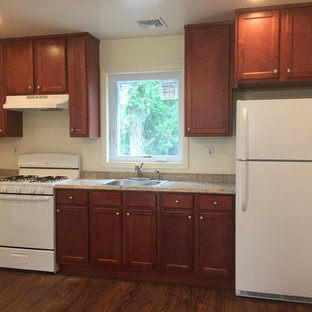 Small single-wall eat-in kitchen in New York with a drop-in sink, shaker cabinets, red cabinets, laminate benchtops, beige splashback, white appliances, vinyl floors, no island and brown floor.