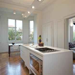 Immagine di una cucina design di medie dimensioni con lavello integrato, ante lisce, ante bianche, top in superficie solida, elettrodomestici in acciaio inossidabile, pavimento in legno massello medio e isola