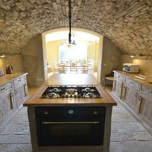 Inspiration for a country kitchen in Florence with an integrated sink, recessed-panel cabinets, distressed cabinets, wood benchtops, travertine splashback, black appliances, limestone floors and with island.