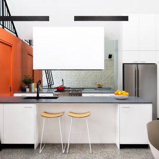 Inspiration for a contemporary galley kitchen in Melbourne with an undermount sink, stainless steel appliances, a peninsula, grey floor, grey benchtop and vaulted.