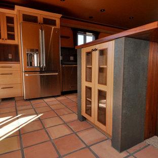 サンルイスオビスポの中くらいのビーチスタイルのおしゃれなキッチン (アンダーカウンターシンク、シェーカースタイル扉のキャビネット、淡色木目調キャビネット、コンクリートカウンター、メタリックのキッチンパネル、磁器タイルのキッチンパネル、シルバーの調理設備、テラコッタタイルの床、赤い床) の写真