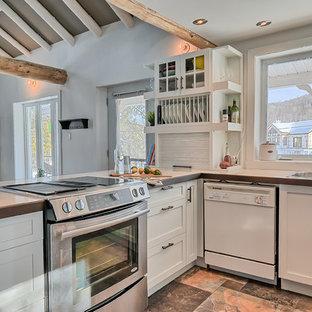 Ispirazione per una cucina eclettica di medie dimensioni con lavello a doppia vasca, ante in stile shaker, ante bianche, top piastrellato, paraspruzzi bianco, paraspruzzi a finestra, elettrodomestici in acciaio inossidabile, pavimento in ardesia e penisola