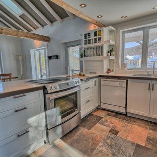 Immagine di una cucina bohémian di medie dimensioni con lavello a doppia vasca, ante in stile shaker, ante bianche, top piastrellato, paraspruzzi bianco, paraspruzzi a finestra, elettrodomestici in acciaio inossidabile, pavimento in ardesia e penisola