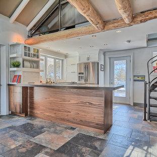 Immagine di una cucina eclettica di medie dimensioni con lavello a doppia vasca, ante in stile shaker, ante bianche, top piastrellato, paraspruzzi bianco, paraspruzzi a finestra, elettrodomestici in acciaio inossidabile, pavimento in ardesia e penisola
