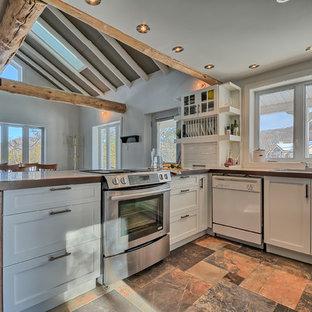 Immagine di una cucina boho chic di medie dimensioni con lavello a doppia vasca, ante in stile shaker, ante bianche, top piastrellato, paraspruzzi bianco, paraspruzzi a finestra, elettrodomestici in acciaio inossidabile, pavimento in ardesia e penisola