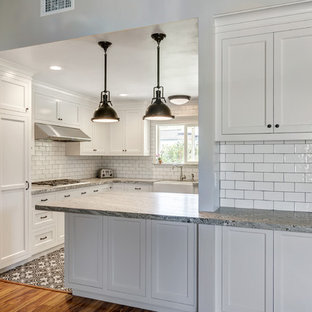 This is an example of a small country galley kitchen pantry in San Diego with a belfast sink, shaker cabinets, white cabinets, granite worktops, white splashback, porcelain splashback, stainless steel appliances, ceramic flooring and a breakfast bar.