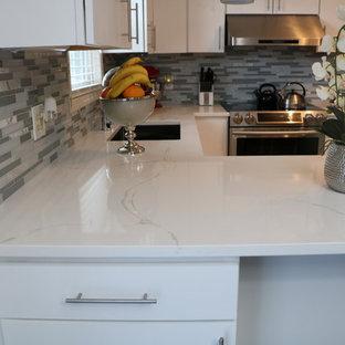 Kleine Moderne Küche in U-Form mit Unterbauwaschbecken, flächenbündigen Schrankfronten, weißen Schränken, Quarzit-Arbeitsplatte, Küchenrückwand in Grau, Rückwand aus Stäbchenfliesen, Küchengeräten aus Edelstahl, Porzellan-Bodenfliesen, Halbinsel und braunem Boden in Grand Rapids