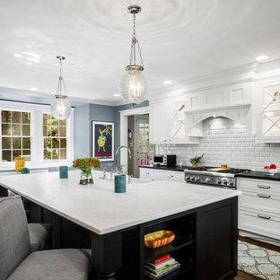 他の地域の広いトランジショナルスタイルのおしゃれなキッチン (エプロンフロントシンク、落し込みパネル扉のキャビネット、白いキャビネット、クオーツストーンカウンター、白いキッチンパネル、サブウェイタイルのキッチンパネル、シルバーの調理設備、濃色無垢フローリング、茶色い床、白いキッチンカウンター) の写真