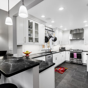 This is an example of a mid-sized modern u-shaped separate kitchen in Other with an undermount sink, shaker cabinets, white cabinets, soapstone benchtops, white splashback, ceramic splashback, stainless steel appliances, porcelain floors, a peninsula, black floor and black benchtop.