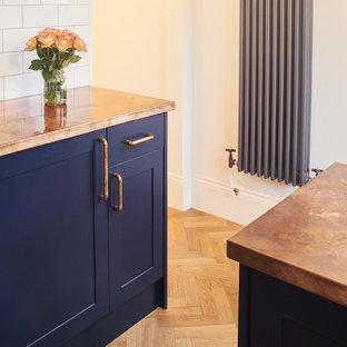 Modelo de cocina en U, urbana, pequeña, cerrada, con fregadero sobremueble, armarios estilo shaker, puertas de armario azules, encimera de cobre, salpicadero blanco, salpicadero de azulejos tipo metro y electrodomésticos de acero inoxidable