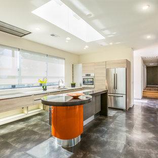 サンフランシスコの大きいモダンスタイルのおしゃれなキッチン (ドロップインシンク、フラットパネル扉のキャビネット、淡色木目調キャビネット、クオーツストーンカウンター、シルバーの調理設備) の写真