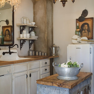 Inspiration for a shabby-chic style kitchen in Other with wood benchtops, white cabinets, white appliances and a farmhouse sink.