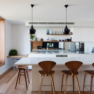 Design ideas for a contemporary l-shaped eat-in kitchen in Sydney with an undermount sink, flat-panel cabinets, white cabinets, mirror splashback, stainless steel appliances, medium hardwood floors, with island, brown floor and white benchtop.