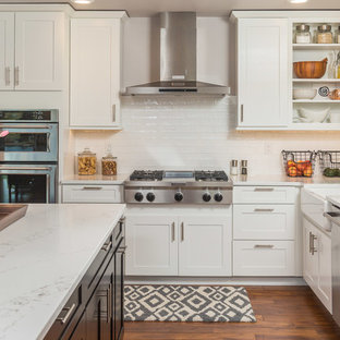 Transitional kitchen photos - Transitional l-shaped kitchen photo in Other with a farmhouse sink, shaker cabinets, white cabinets, white backsplash, stainless steel appliances and an island