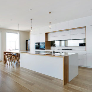 This is an example of a large contemporary galley open plan kitchen in Sydney with a double-bowl sink, quartz benchtops, mirror splashback, black appliances, light hardwood floors, flat-panel cabinets, white cabinets, with island and beige floor.