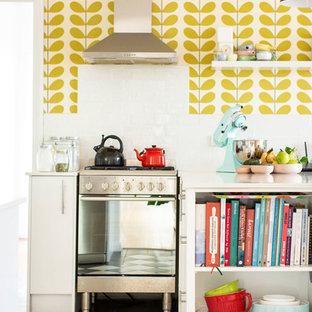 ニューカッスルのエクレクティックスタイルのおしゃれなキッチン (フラットパネル扉のキャビネット、白いキャビネット、シルバーの調理設備の、マルチカラーの床、白いキッチンカウンター) の写真