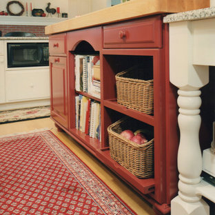 This is an example of a large country u-shaped open plan kitchen in Boston with open cabinets, red cabinets, wood benchtops, light hardwood floors and multiple islands.
